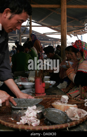 Flower Hmong women eating traditional tribal food at the market in Bac Ha, Vietnam, Southeast Asia - Stock Photo