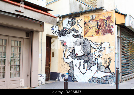 Graffiti painting on the wall in the small street of central Paris - Stock Photo