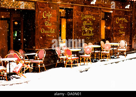 Wooden parisian coffee house with it's sidewalk tables and chairs in winter with the snow falling - Stock Photo