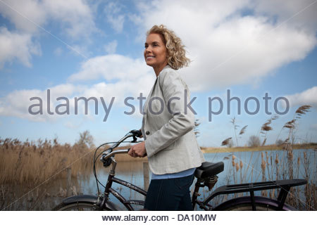 A mature woman standing beside a lake with a bicycle - Stock Photo