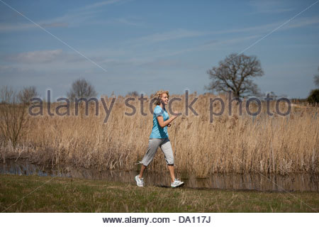 A mature woman power walking in the countryside - Stock Photo
