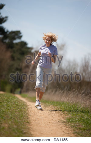 A mature woman running along a country path - Stock Photo