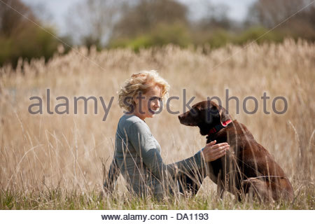 A mature woman sitting on the grass stroking her dog - Stock Photo