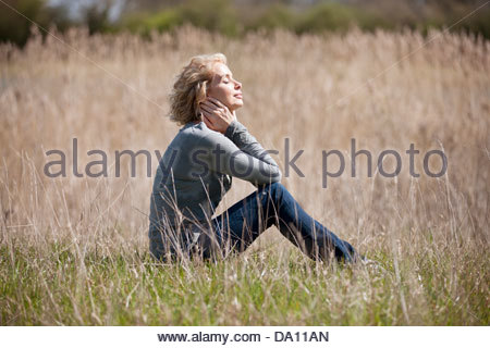 A mature woman sitting on the grass, enjoying the sunshine - Stock Photo