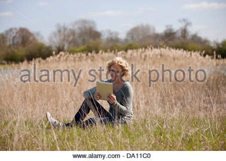 A mature woman sitting in long grass, looking at a digital tablet - Stock Photo