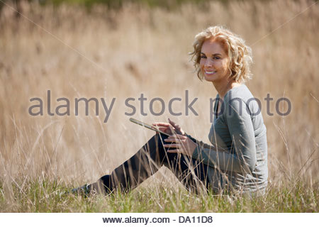 A mature woman sitting in long grass, using a digital tablet - Stock Photo