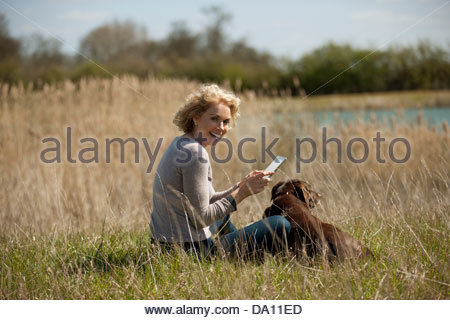 A mature woman sitting in long grass with her dog, looking at a digital tablet - Stock Photo