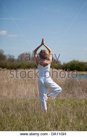A mid adult woman practising yoga in the countryside in summertime - Stock Photo