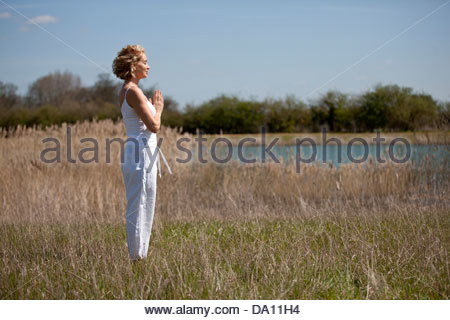A mid adult woman practicing yoga in the countryside in summertime - Stock Photo