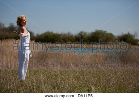 A mature woman practicing yoga in the countryside in summertime - Stock Photo