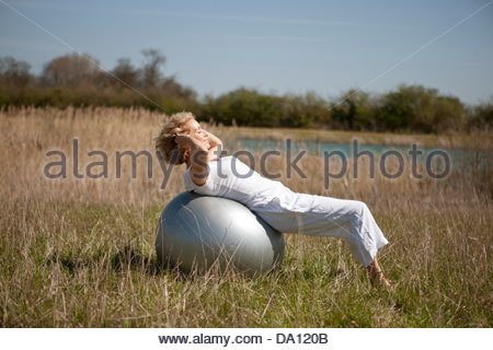 A mature woman exercising on an exercise ball - Stock Photo