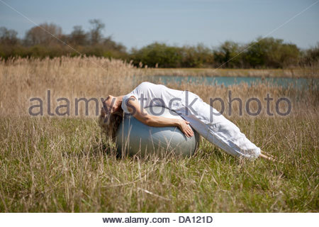 A mature woman stretching on an exercise ball - Stock Photo