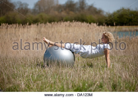 A mature woman exercising with an exercise ball - Stock Photo