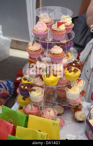 Home made cakes on sale by volunteer mums on a stall at a primary school summer fair - Stock Photo