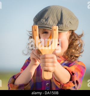 Funny kid shooting wooden slingshot against blue summer sky background. - Stock Photo
