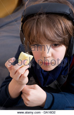 kids watching tv and eating. kids kid child children boy eating food slice of apple watching tv television - stock photo and