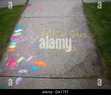A colorful message and design are done in chalk on a sidewalk. - Stock Photo