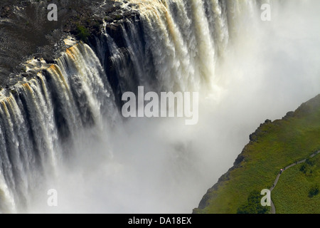 Tourists on pathway viewing Victoria Falls or 'Mosi-oa-Tunya' (The Smoke that Thunders), and Zambezi River, Zimbabwe - Stock Photo
