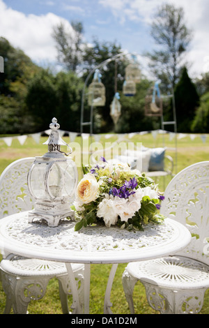 garden decorated for wedding reception with bunting, lanterns and bird cages in a vintage shabby chic theme with - Stock Photo