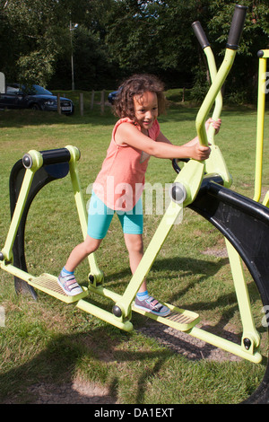 Children exercising at an outdoor gymnasium in a public park in southern England. - Stock Photo