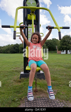 Child exercising at an outdoor gymnasium in a public park in southern England. - Stock Photo