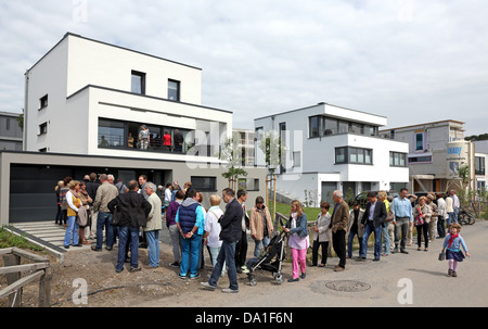 Visitors queue around to visit a newly build single-family house in the Lake Phoenix Estate of Dortmund, Germany - Stock Photo