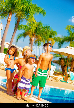 Cute big family standing near poolside and look up in the sky, enjoying summer holiday, facial expression - Stock Photo