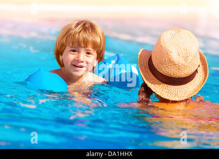 Closeup on cute little boy with mother swimming in the pool, happy family having fun in water, summer vacation - Stock Photo