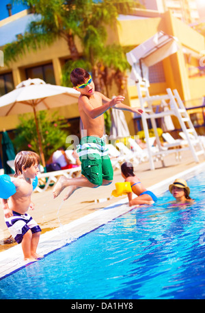 Happy family having fun in the pool, son jumping into the water, relaxed in aquapark, beach resort, summer vacation - Stock Photo