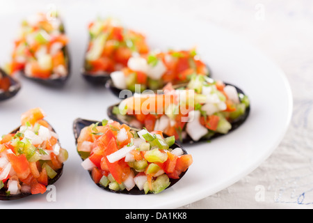 Steamed mussels with vegetable mince on a white dish - Stock Photo