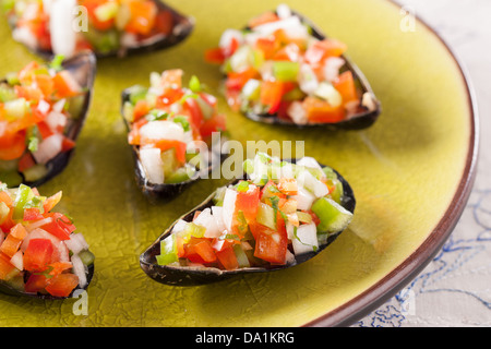 Steamed mussels with vegetable mince on a green dish - Stock Photo