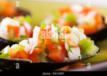 Steamed mussel with vegetable mince on a green dish - Stock Photo
