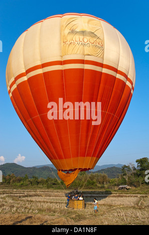Vertical close up view of a hot air balloon preparing for take off in the countryside near Vang Vieng. - Stock Photo