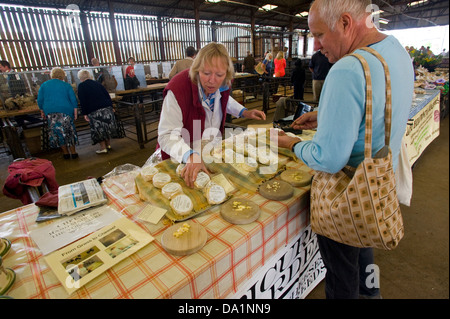 Customer buying cheese from stall selling Wold cheeses at monthly farmers market in Malton Ryedale North Yorkshire - Stock Photo