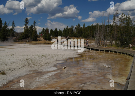 Blue sky white clouds view boardwalk tourists crossing orange bacterial overflow Silex Spring, Lower Geyser Basin, - Stock Photo
