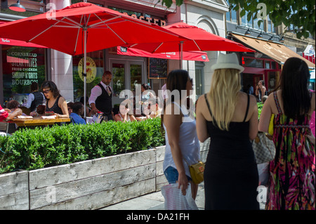Patrons sit at the outdoor cafe of the Red Rooster restaurant on Lenox Avenue in the neighborhood of Harlem - Stock Photo