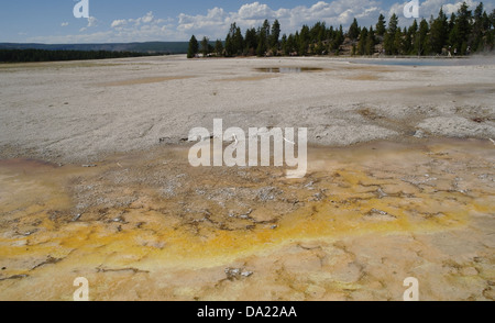 Blue sky view orange bacterial mat overflow Silex Spring to grey sinter Celestine Pool, Lower Geyser Basin, Yellowstone, - Stock Photo