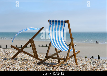Two empty blue striped deckchairs blowing in the wind on a shingle and sand beach at bognor regis west sussex Uk - Stock Photo