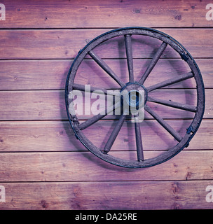 Vintage wooden wheel on the old wall - Stock Photo
