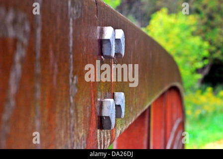 Close-up of four hexagonal screws on rusted steel railing. - Stock Photo