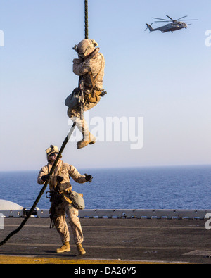 A US Marine assigned to Battalion Landing Team fast ropes from a CH-53 Super Stallion helicopter during familiarization - Stock Photo