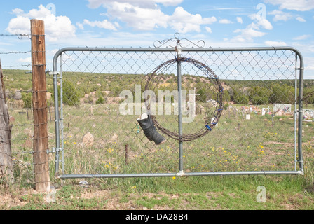 A cowboy boot hangs on an entrance gate to a cemetery near Anton Chico, in New Mexico. - Stock Photo