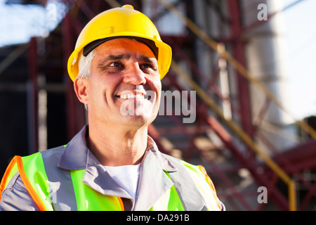 happy middle aged chemical industry worker in plant - Stock Photo