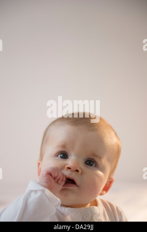Portrait of baby girl (6-11 months) sitting in bed with stack of books - Stock Photo