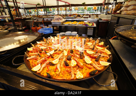 Paella, - Spanish dish made of rice and seafood in fairground on April in Seville, Spain - Stock Photo