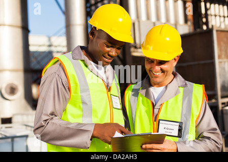 two heavy industry workers working in plant - Stock Photo