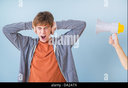 Teenage boy (14-15) with hands on ears - Stock Photo