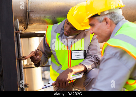 two mechanical engineers working on fuel pipeline in plant - Stock Photo