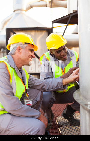 two petrochemical technicians inspecting fuel tank in plant - Stock Photo