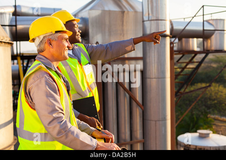 two chemical factory workers working in plant - Stock Photo